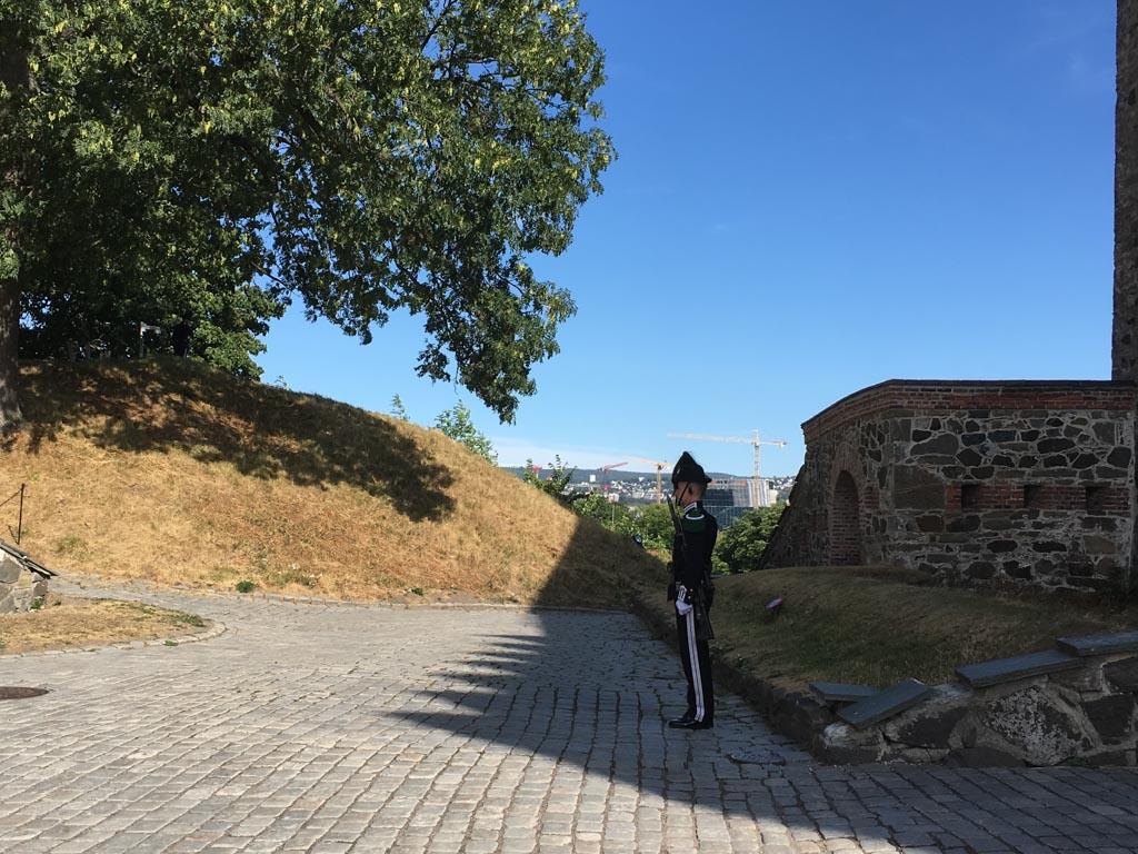 Een wachter voor het Akershus. We hebben een beetje medelijden met de geüniformeerde man die uren in de verzengende hitte staat.