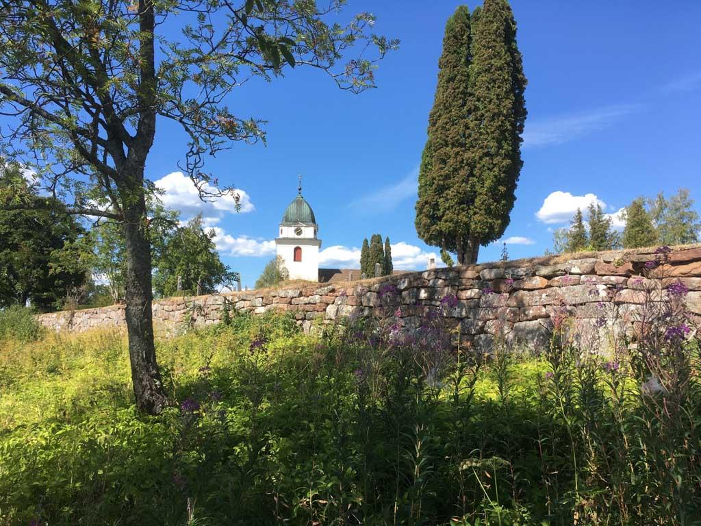 De Svenska Kyrkann. Voor bezoekers aan het kerkhof dat er omheen ligt, kan het fenomenale uitzicht niet anders dan troostend zijn.