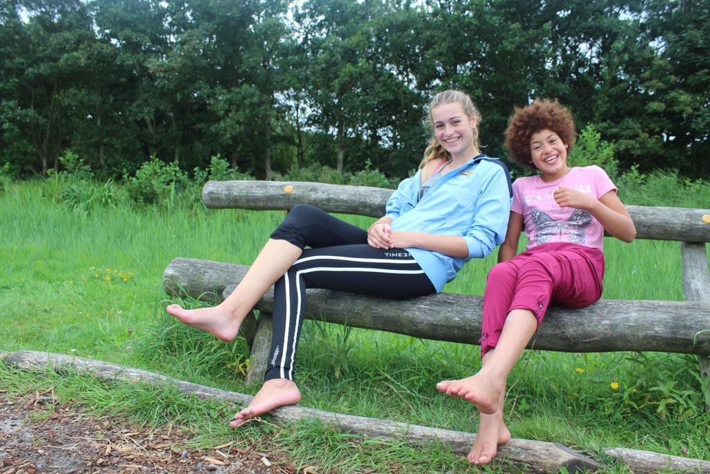De benen strekken op een bungelbank op het blote voetenpad.