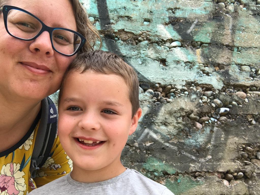 Moeder - zoon selfie bij een bunkerwand met graffiti.