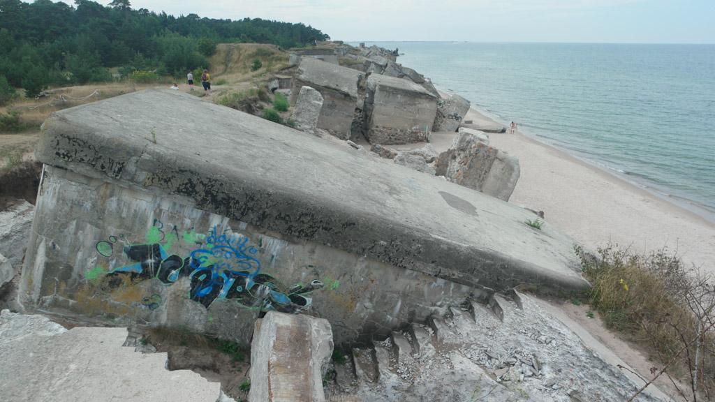 Een hele rij ingestorte bunkers op de grens van de duinen en het strand.