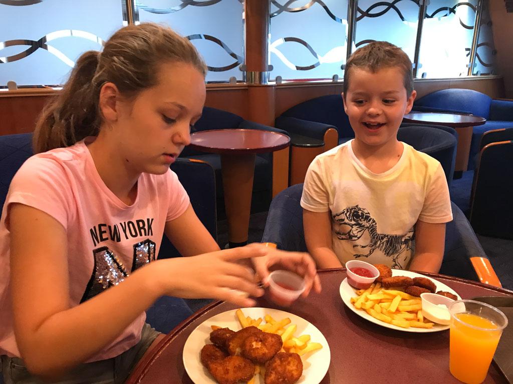 De kinderen kiezen voor het kindermenu met kipnuggets.