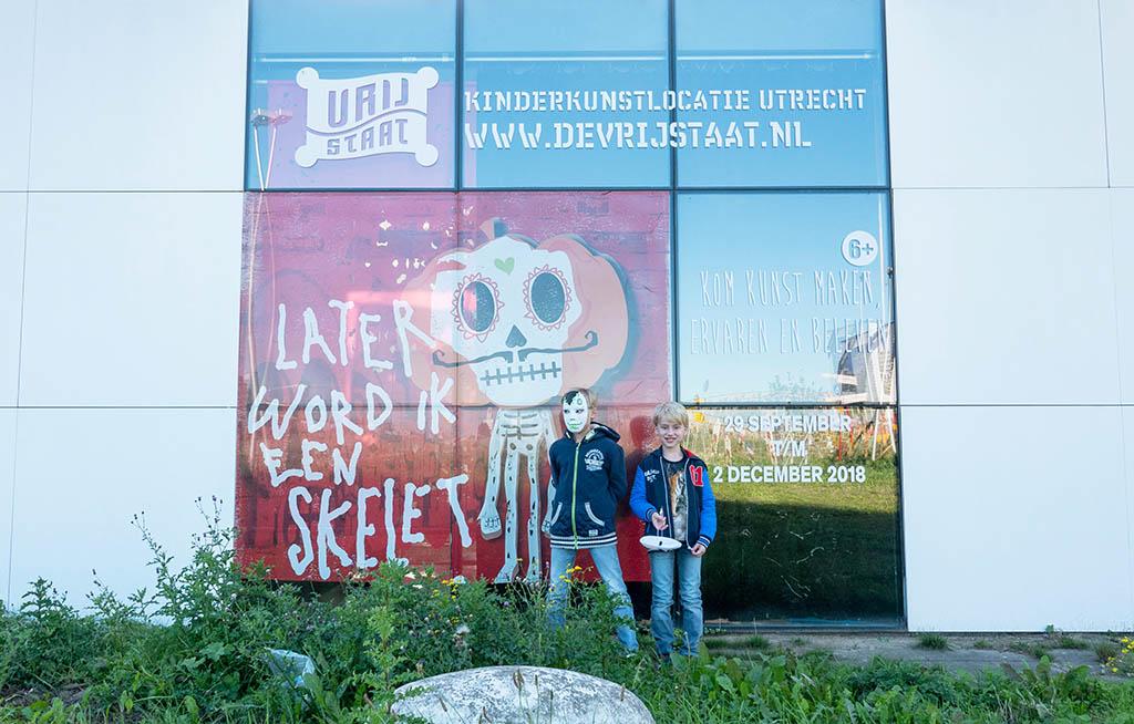 Met hun maskers op de foto bij de poster van LATER WORD IK EEN SKELET