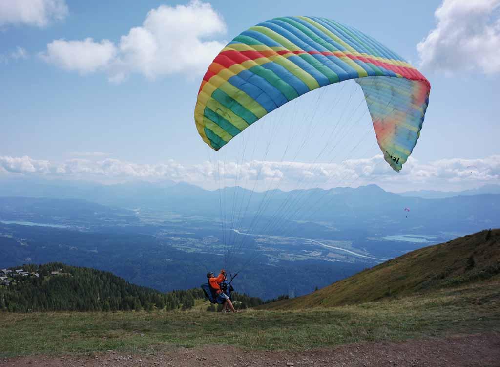 De ene na de andere paraglider rent de berg af en zweeft leukste-kabelbanen-in-karinthie