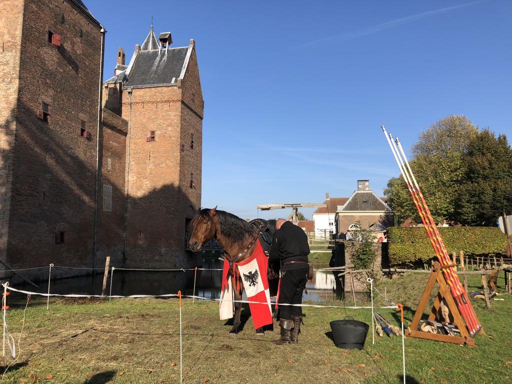 De ridders maken hun paarden klaar voor de strijd.