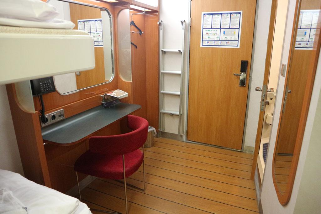 Met links een klein bureautje met stoel en rechts achter de deur is de badkamer.
