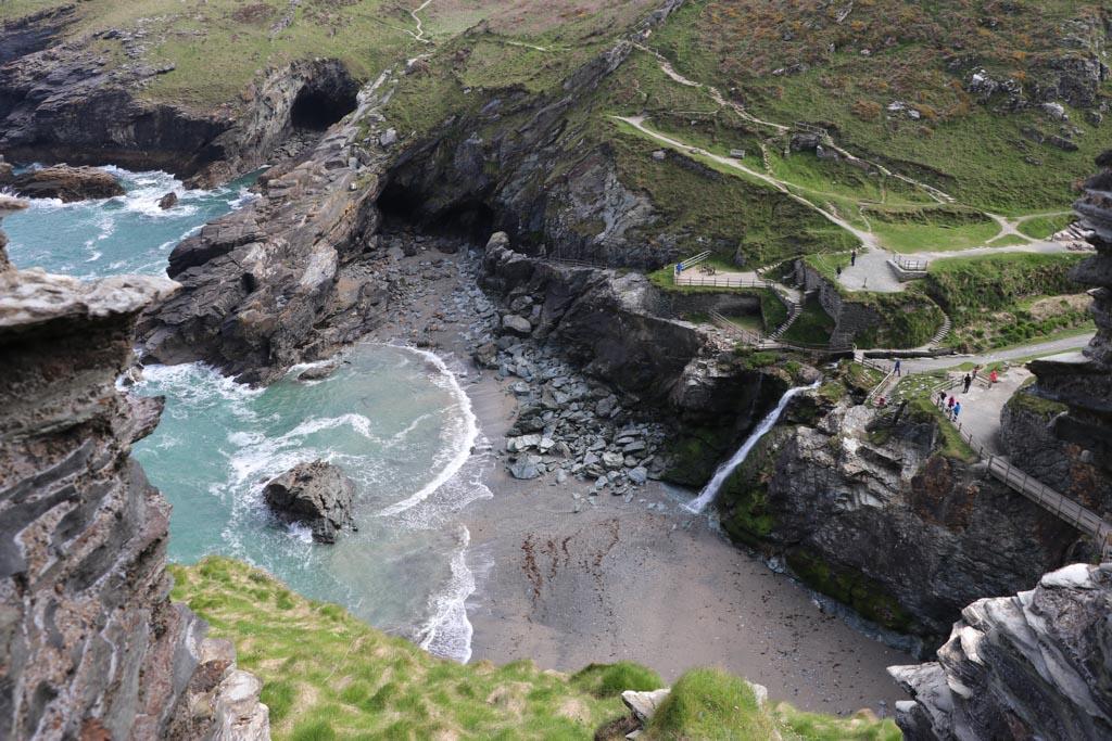 Daar beneden is de grot waar tovenaar Merlijn aan Arthur de geheimen van de magie onthulde. Er ligt altijd water in de grot en hij is alleen bij eb bereikbaar.