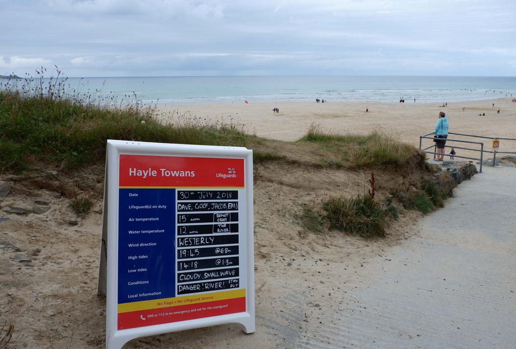 Langs de toegangsweg richting strand staan borden met informatie over de aanwezigheid van strandwachten en de tijden van eb en vloed