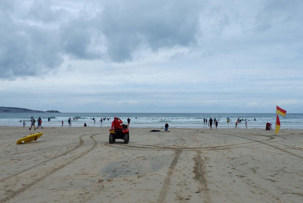 De gekleurde vlaggen geven aan waar gezwommen mag worden en de strandwacht houdt toezicht.