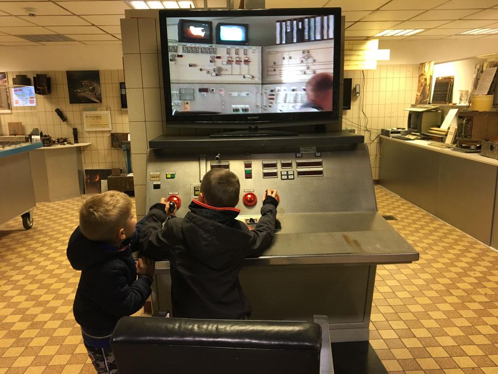 De jongens bedienen een machine voor de bewerking van staal.