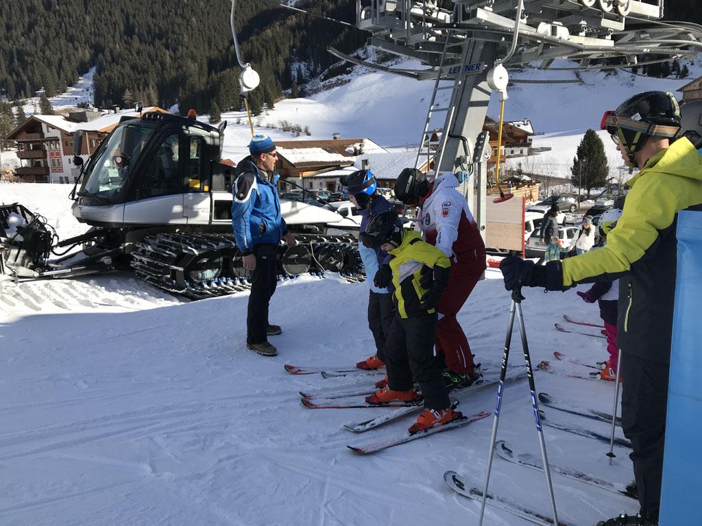 Samen met de skileraar gaan ze met de sleeplift omhoog.