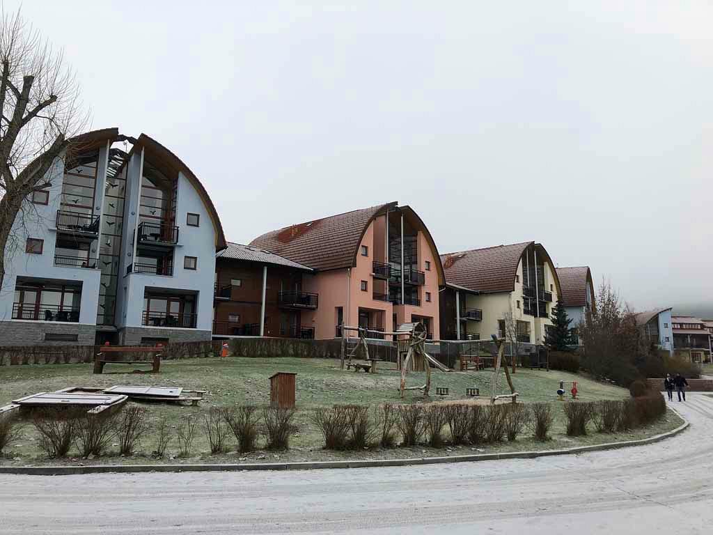 De huizen en appartementen op Landal Marina Lipno park kijken uit over het meer en hebben een opvallende bouw.