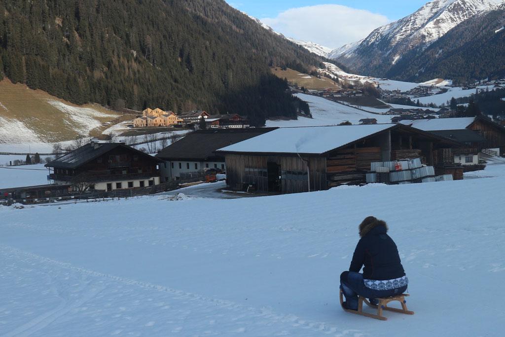 Saskia zoeft op de houten slee de heuvel af.