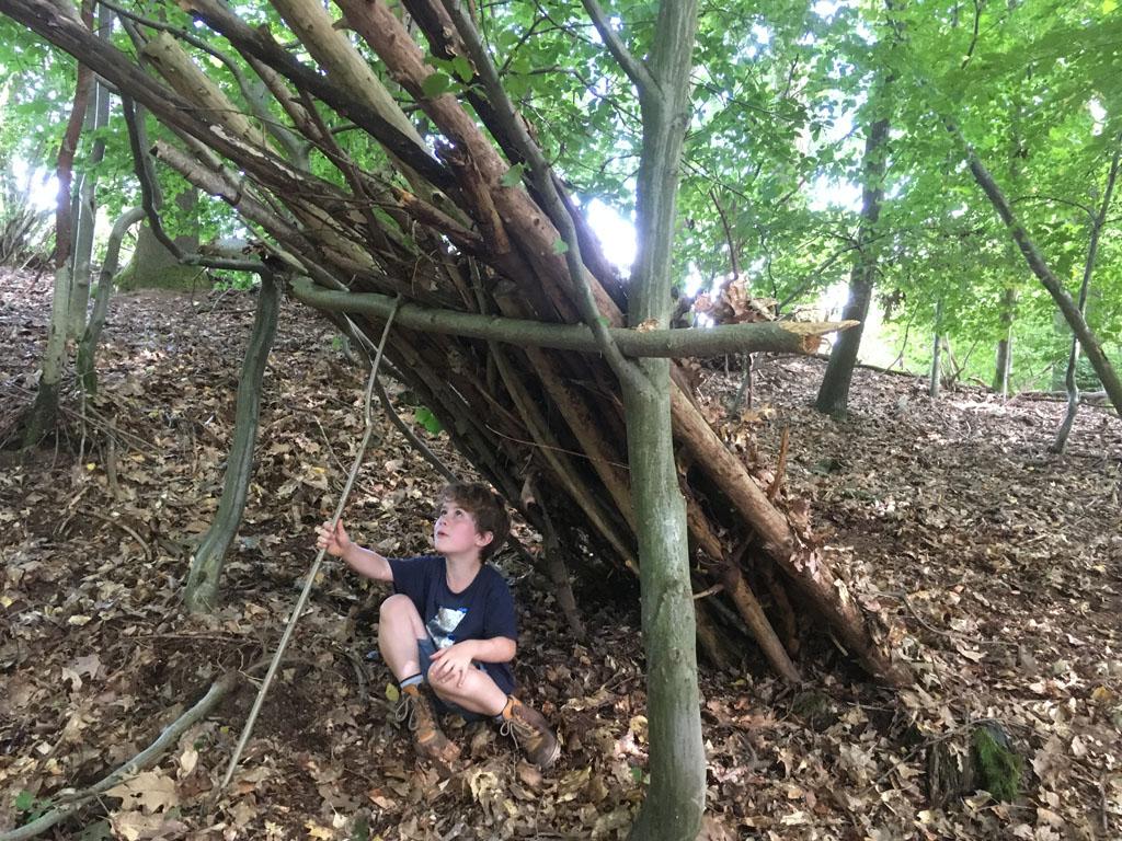 Als we tijdens het wandelen pauzeren, slaan de kinderen aan het huttenbouwen.