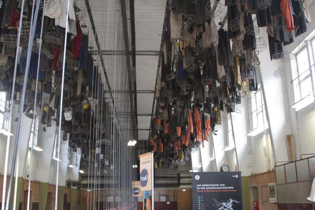 De mijnwerkerskleding hangt aan het plafond in de omkleedruimte.