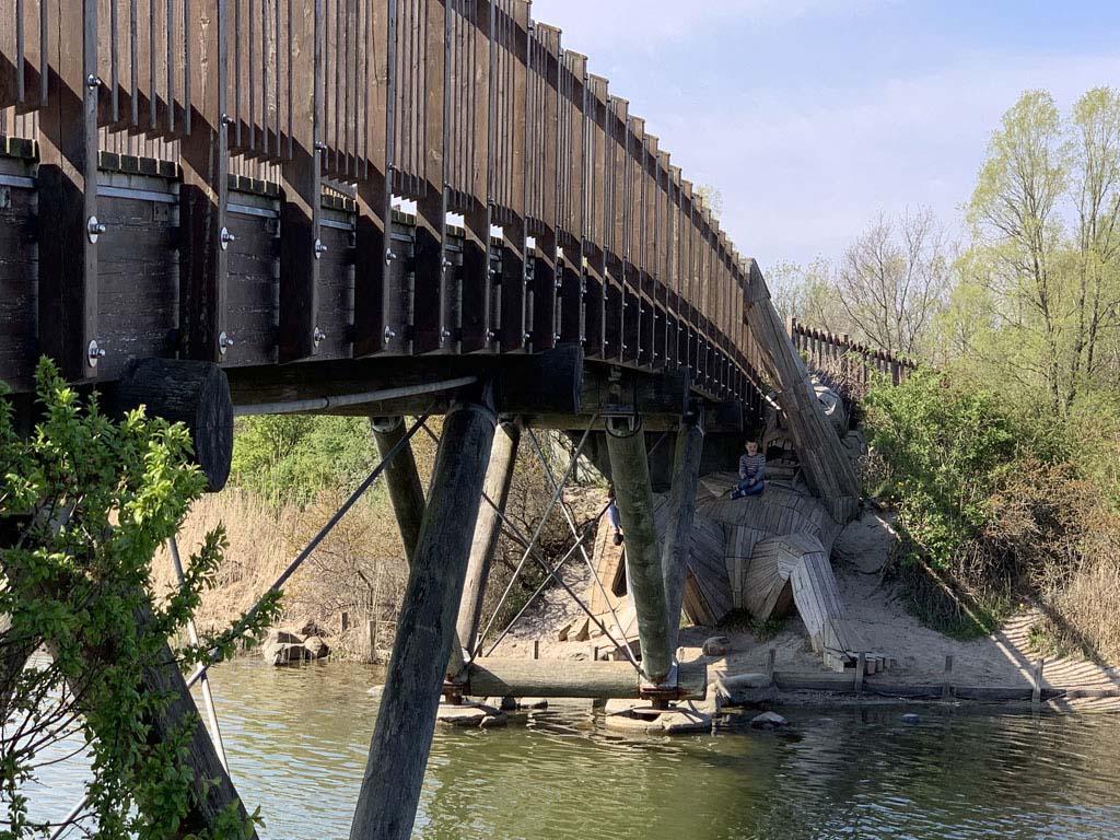Houten reus Oscar ligt onder de brug.