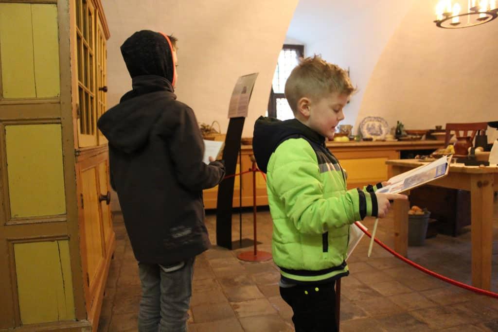 T. van 5 jaar doet een speurtocht met plaatjes, K. van 7 jaar mag zelf lezen en schrijven.