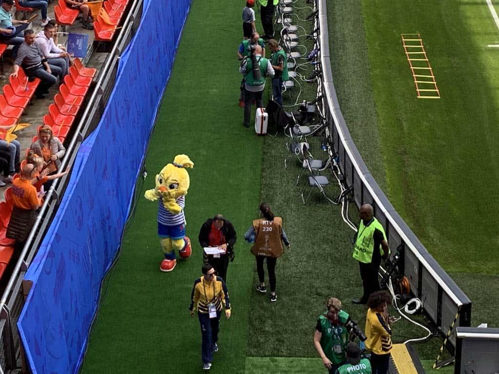De mascotte van het toernooi maakt een rondje langs het veld.
