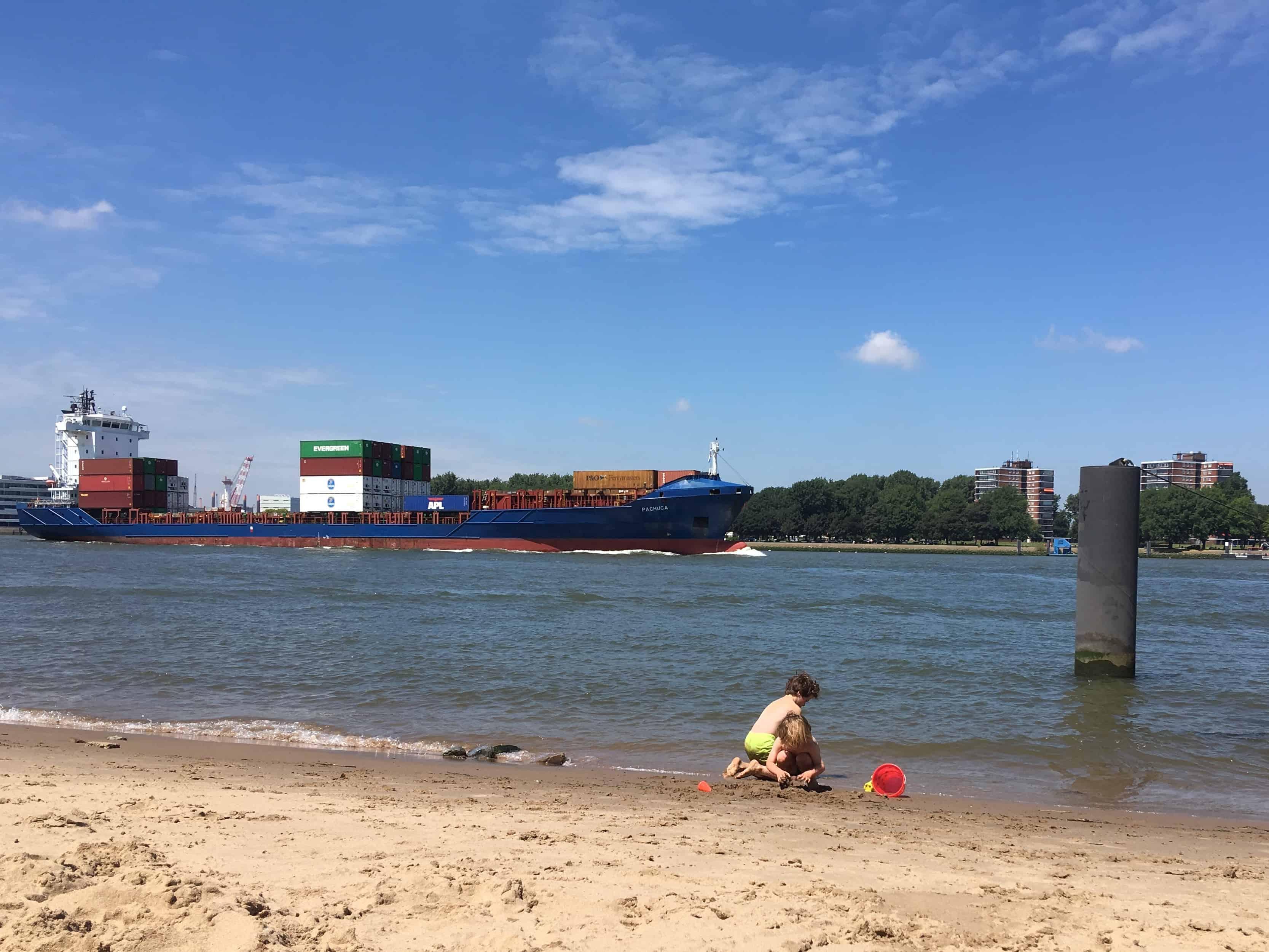 Greppels graven met een vrachtschip op de achtergrond.
