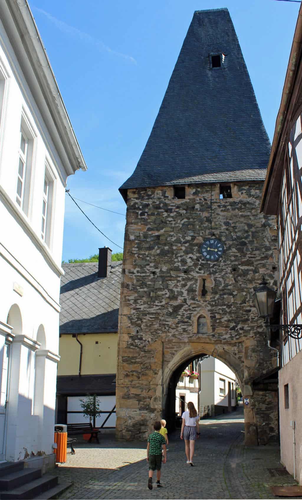 Onder de klokkentoren door, waarna de historische stadskern van Herrstein begint