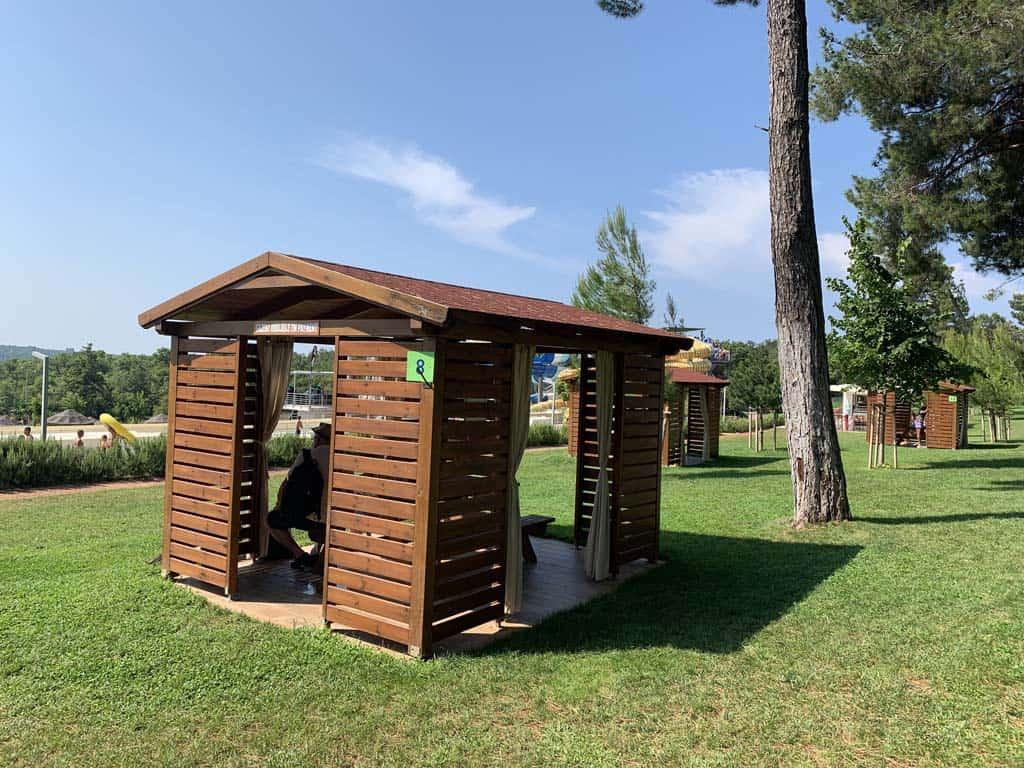 Op de ligweide zijn dit soort huisjes met een picknickbank te huur. Je kunt ze afschermen tegen zonlicht met gordijnen.