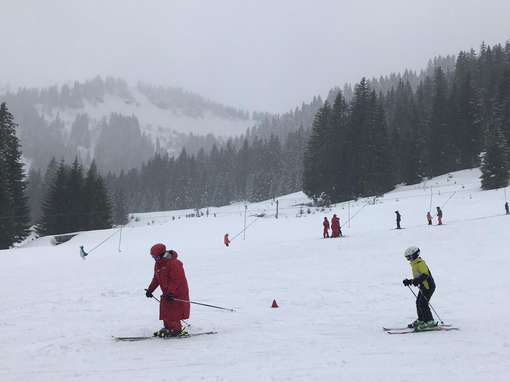 Hij skiet braaf achter de skileraar aan.