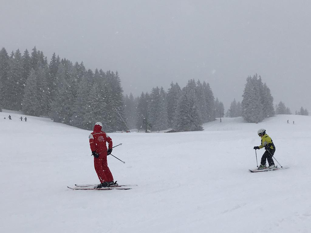 Achter de skileraar aan skiën en bochtjes maken.