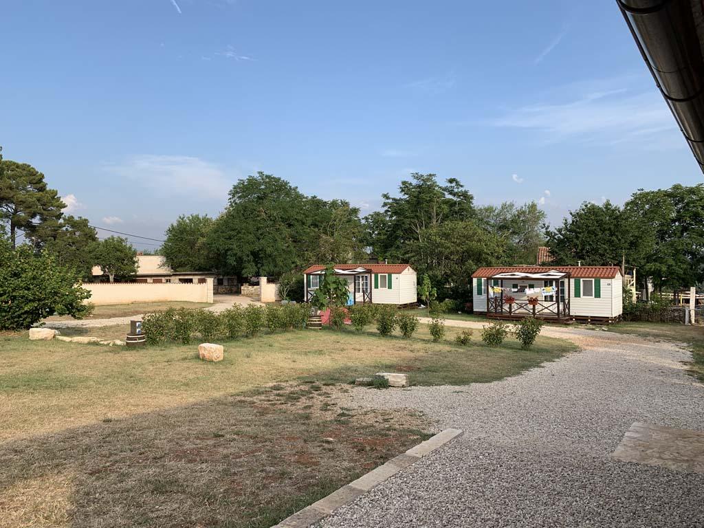 De kampeerplekken bij het sanitairgebouw zijn van elkaar gescheiden door een haagje.
