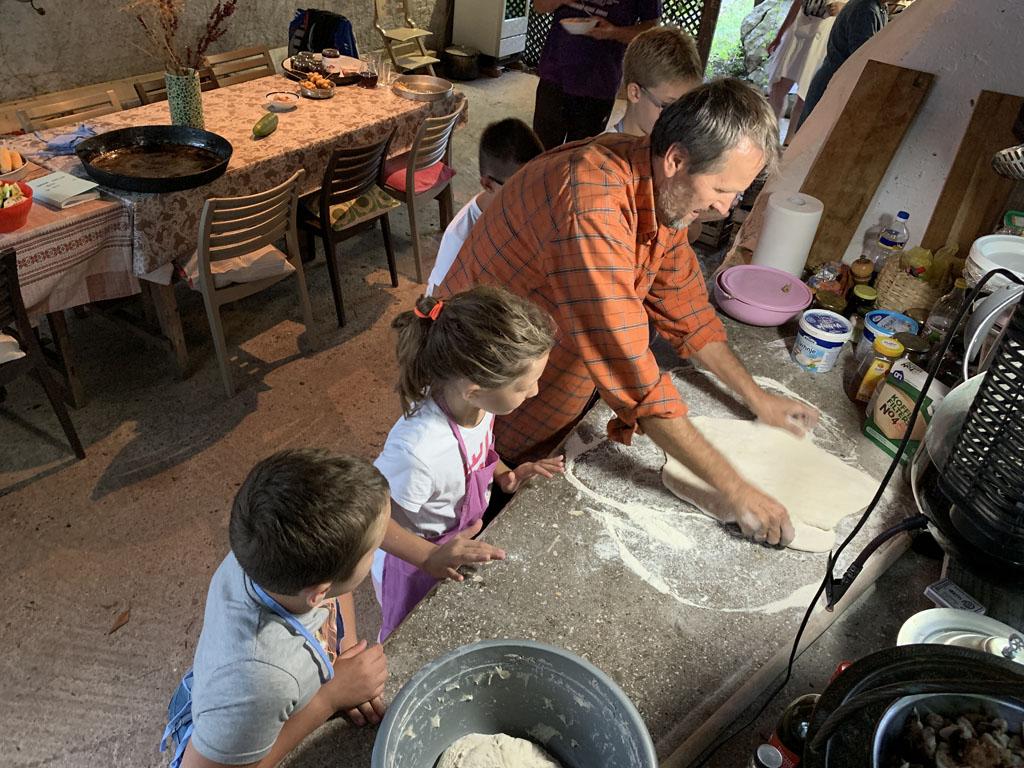 De kinderen helpen met het maken van de pizza's.