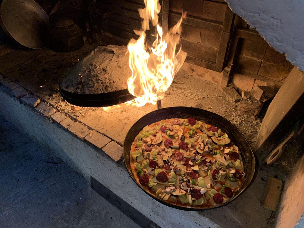 De grote pizzapan gaat op het vuur.