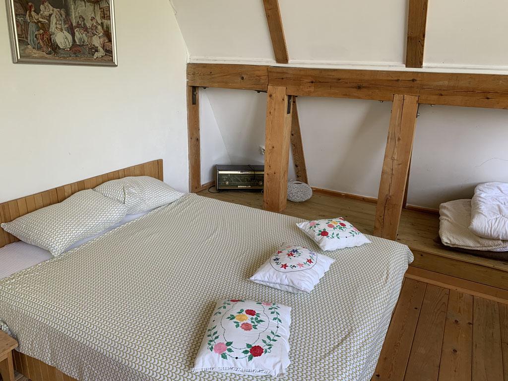 Het 2-persoons bed in de woon- en slaapkamer.