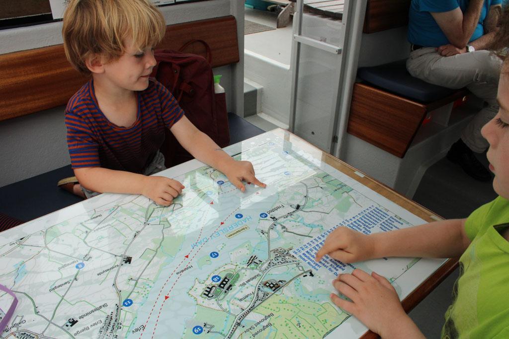 De kinderen houden de vaarroute goed bij op de kaart die in de boot op onze tafel ligt.