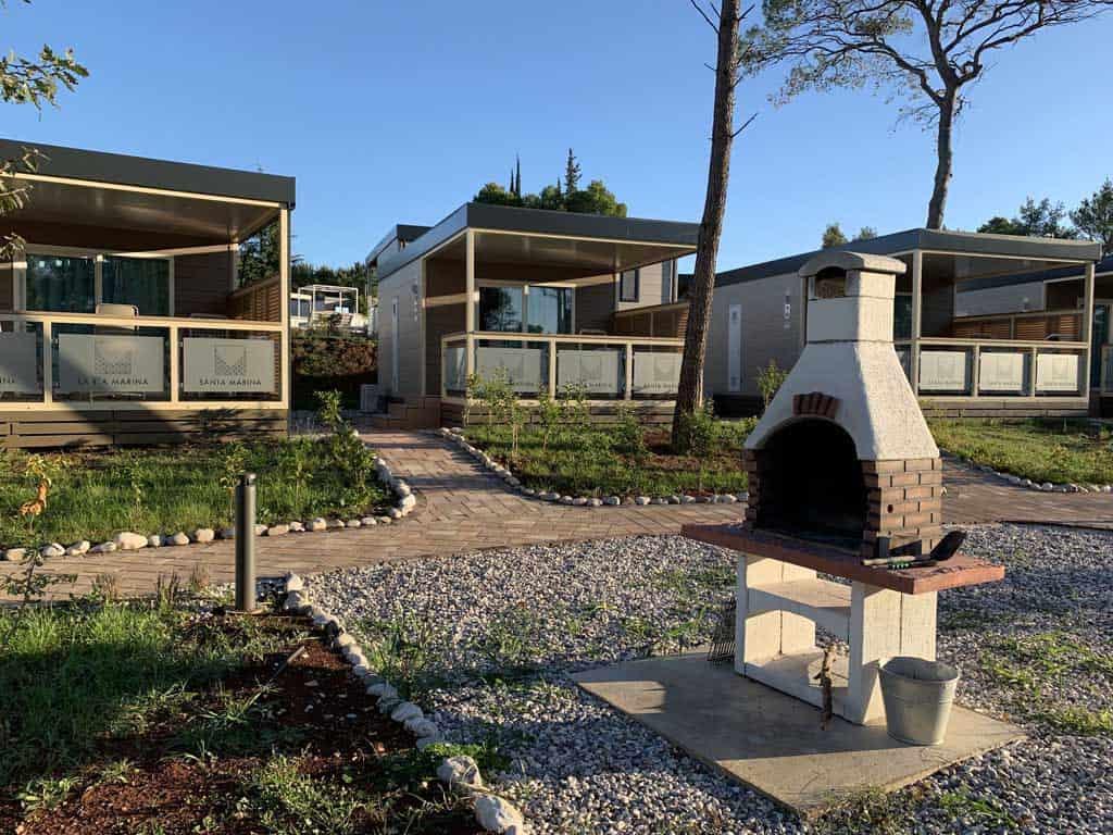 Deze mobil homes staan rondom een pleintje met een gezamenlijke barbecue.
