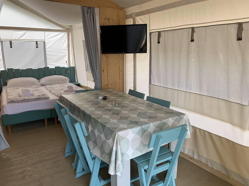 Binnen staat een eetkamertafel voor 6 personen. De slaapkamer daarachter is af te sluiten met een gordijn.