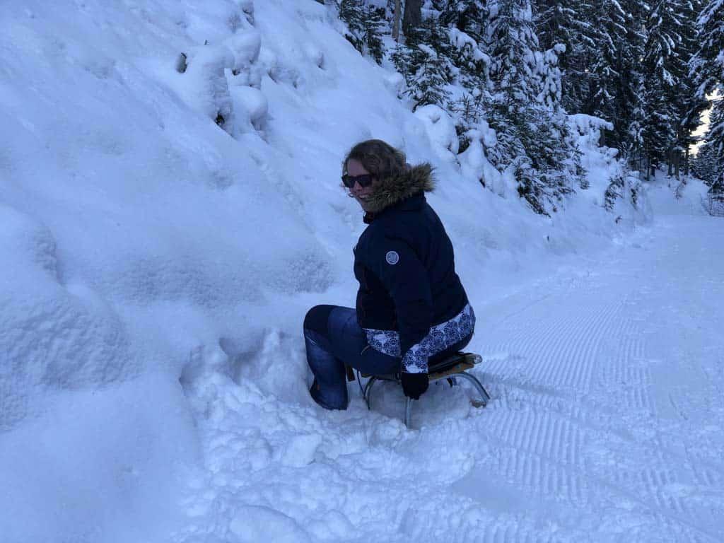 Ik ben niet goed in rodelen en lig met slappe lach alweer vast in de sneeuw naast het pad.
