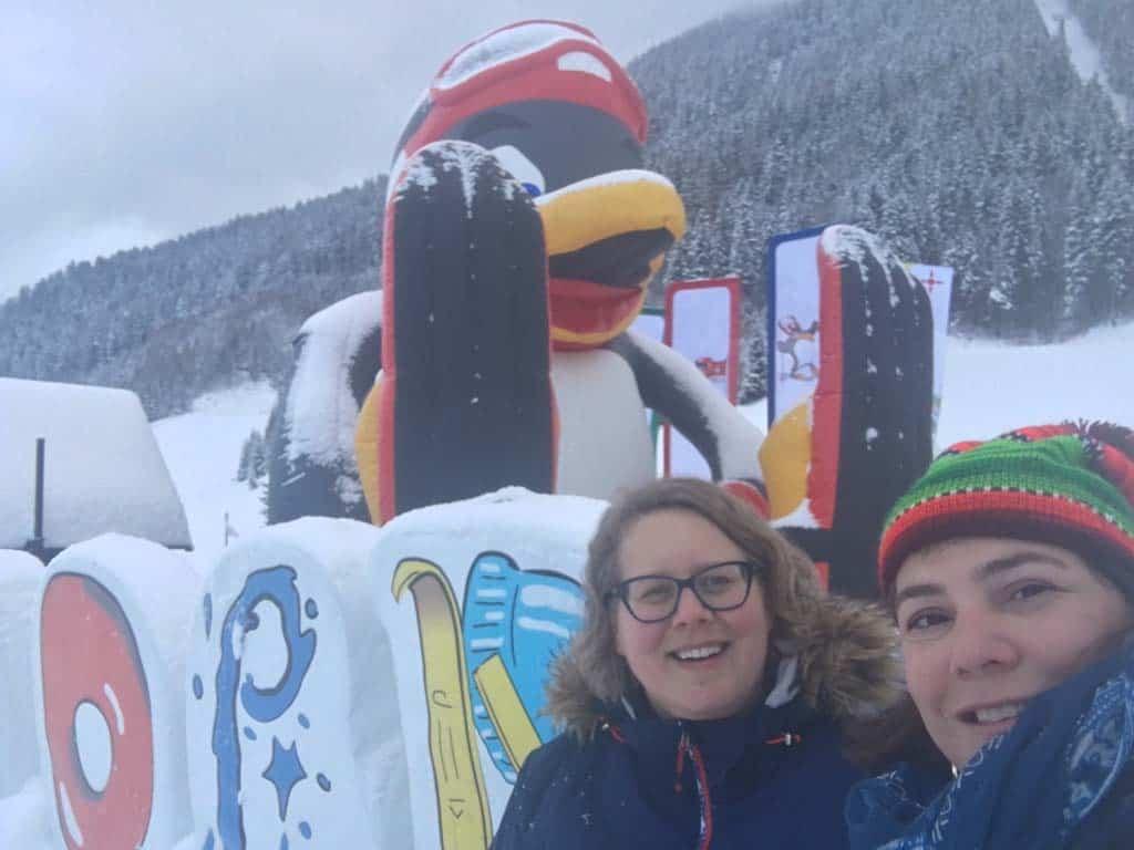 Selfie met op de achtergrond Bobo de pinguin die we overal tegenkomen in skigebied Achensee.
