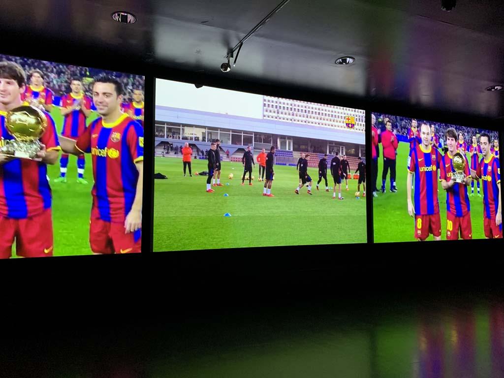 We bekijken hoogtepunten van FC Barcelona op een grote wand met beeldschermen.