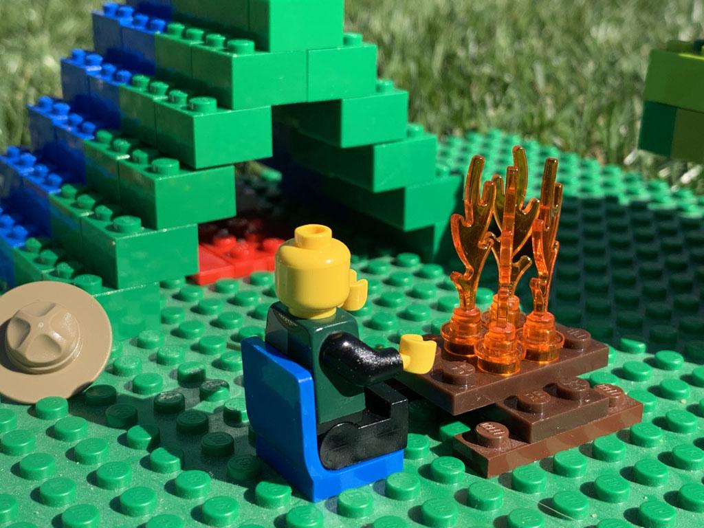 Het mannetje heeft z'n hoed weggelegd en het vuurtje aangemaakt. Op de achtergrond zie je de tent met daarin een bed.