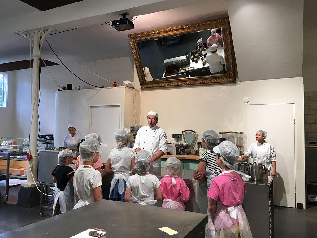 De chocolatier legt uit waar cacaobonen groeien en hoe er chocolade van wordt gemaakt.