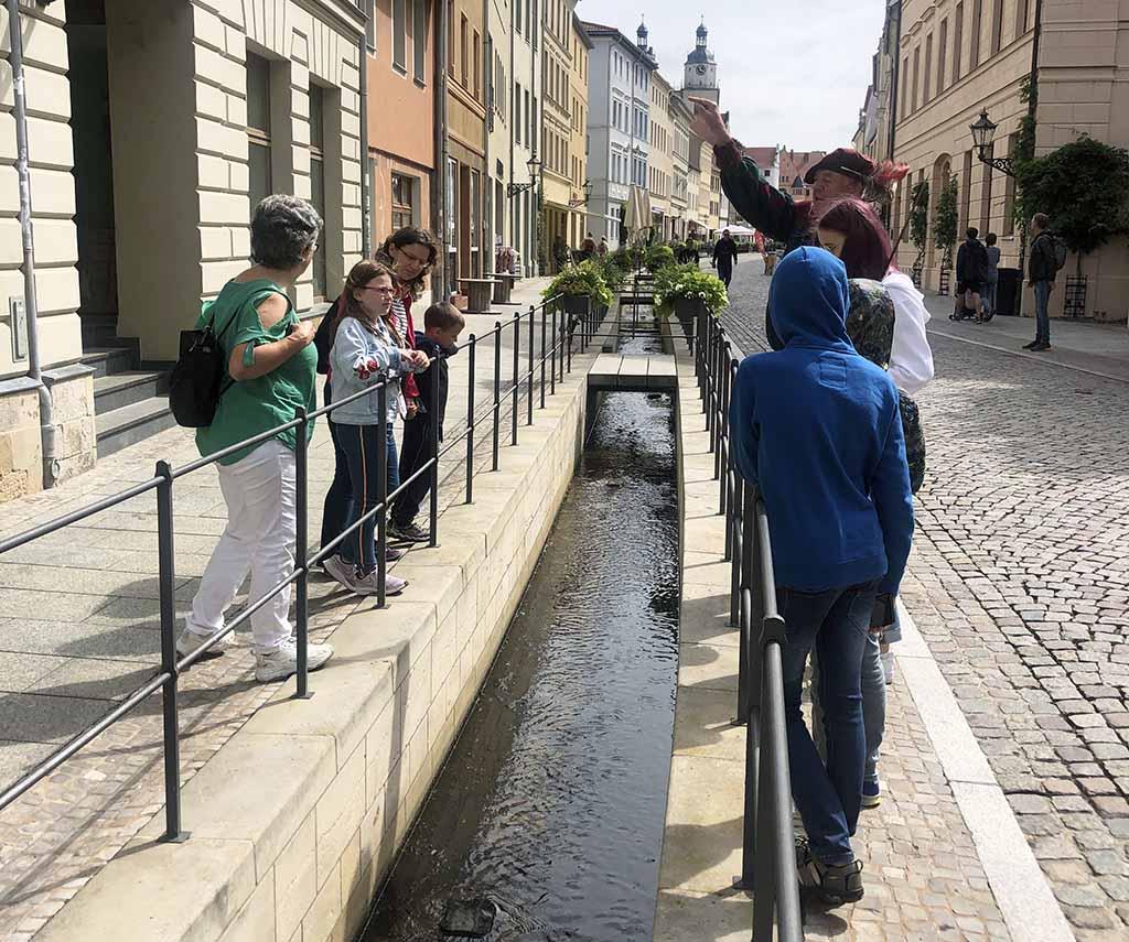 Onze gids vertelt over de beken die door de stad lopen die vroeger als riool gebruikt werden