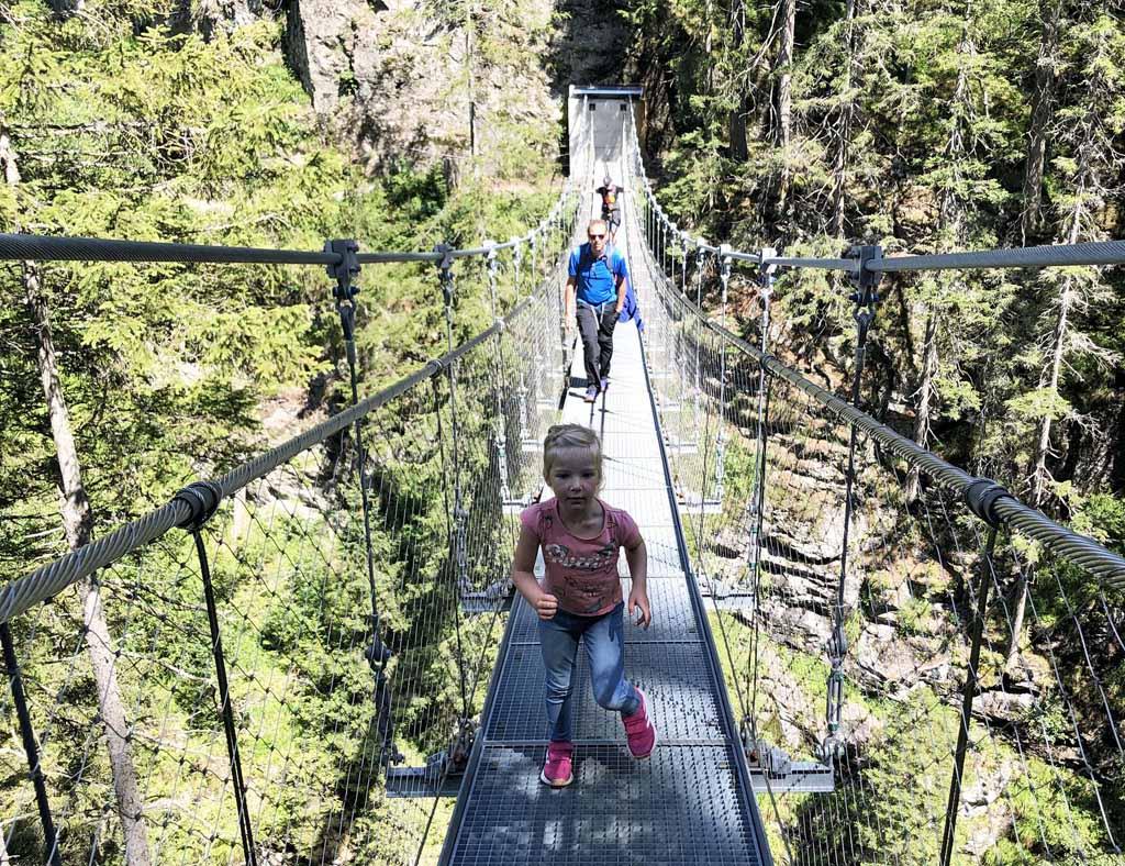 We zien de diepte onder ons vanaf deze toffe hangbrug in de regio Schladming-Dachstein met onze kinderen.
