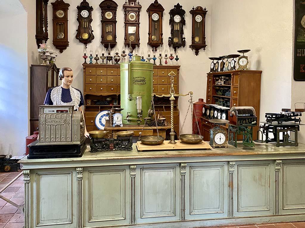 We zien een klokkenwinkel, een kruidenier en een oud koffiewinkeltje op de begane grond