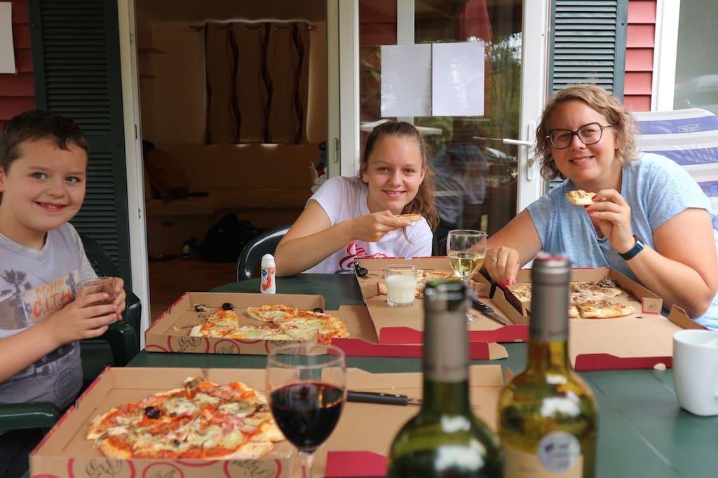 Op ons eigen terras genieten van een lekkere afhaalpizza van het restaurant dat bij de camping hoort.